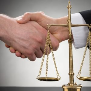 Lawyer and SEO expert shake hands behind justice scales.